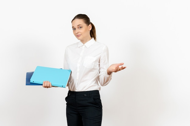 Employé de bureau féminin en chemisier blanc tenant des documents sur blanc