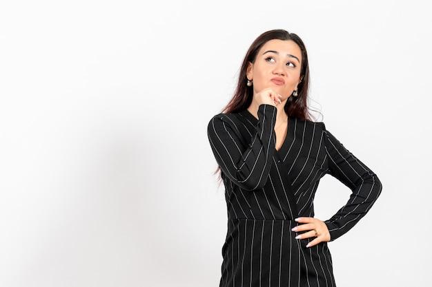 Employé de bureau féminin en costume noir strict avec expression de pensée sur blanc