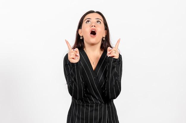 Employé de bureau féminin en costume noir strict regardant plafond sur blanc
