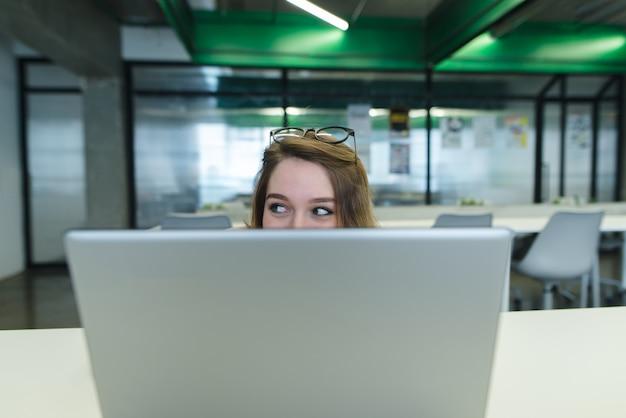 Employé de bureau de fille assis au bureau sur le lieu de travail et se cachant derrière un ordinateur portable