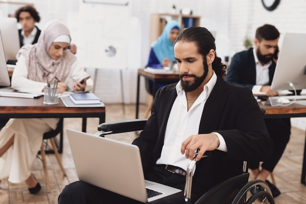 Employé de bureau en homme arabe en fauteuil roulant à l'ordinateur portable.