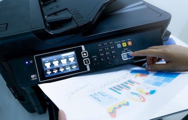 L'employé de bureau imprime du papier sur une imprimante laser multifonction copiez, imprimez, scannez et télécopiez