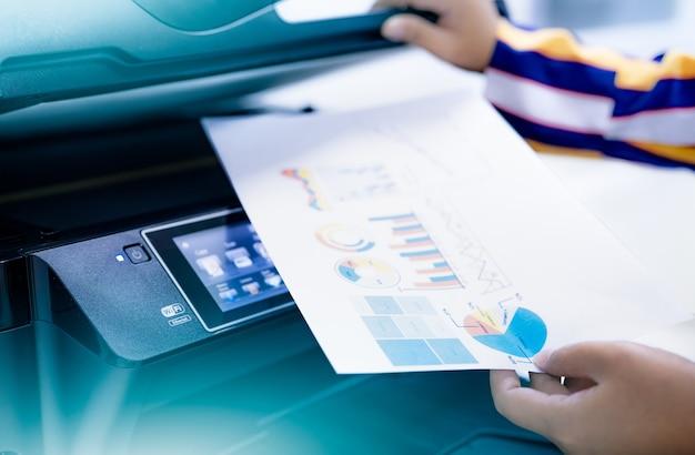 Employé de bureau imprimer du papier sur une imprimante laser multifonction. copiez, imprimez, numérisez et télécopiez au bureau. technologie d'impression moderne. photocopieuse. travail sur documents et papiers. scanner. travail de secrétaire.