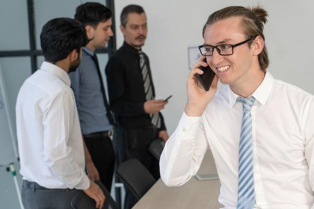 Employé de bureau joyeux apprenant de bonnes nouvelles de la conversation téléphonique.