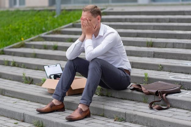 Un employé de bureau licencié est assis sur les marches. l'homme ne sait pas quoi faire ensuite. à côté se trouve une boîte en carton avec de la papeterie.