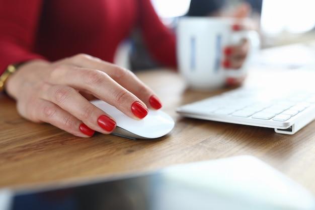 Employé de bureau à la main avec manucure rouge sur les ongles