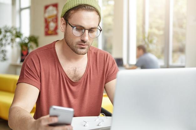 Un employé de bureau masculin intelligent est assis au café, porte des lunettes et des vêtements à la mode