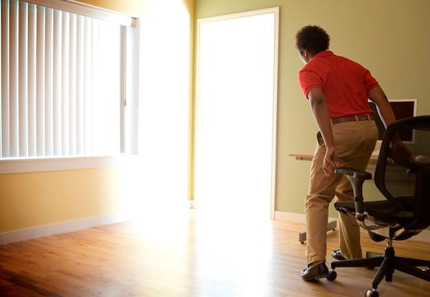 Employé de bureau masculin se levant d'une chaise pour enquêter sur les inondations de lumière par la porte