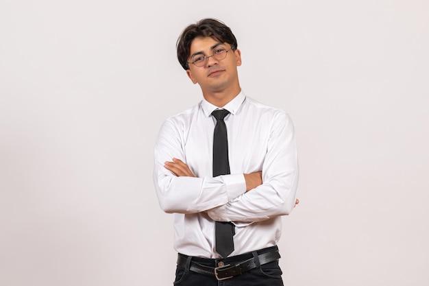 Employé de bureau masculin de vue de face posant sur le travail humain de bureau de travail de mur blanc