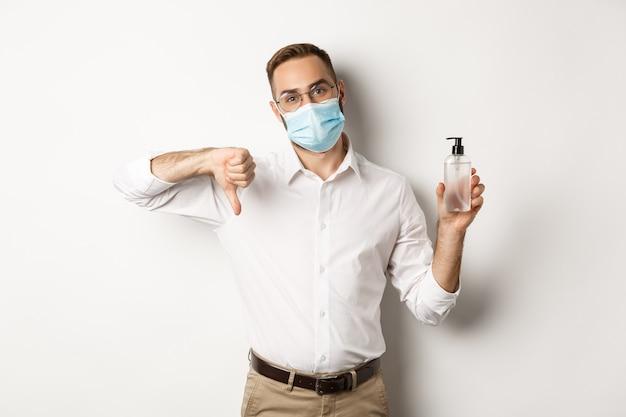 Employé de bureau en masque médical mécontent, montrant un désinfectant pour les mains et le pouce vers le bas, debout