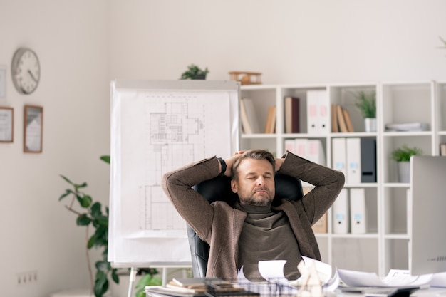 Employé de bureau mature en tenues de soirée assis dans un fauteuil par bureau tout en se concentrant sur le travail ou se détendre à la pause