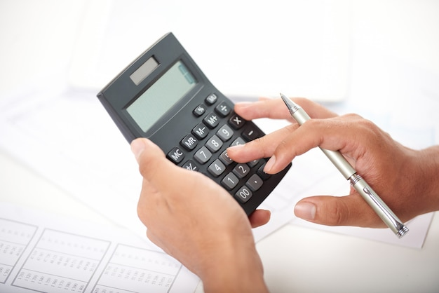 Employé de bureau méconnaissable à l'aide de la calculatrice