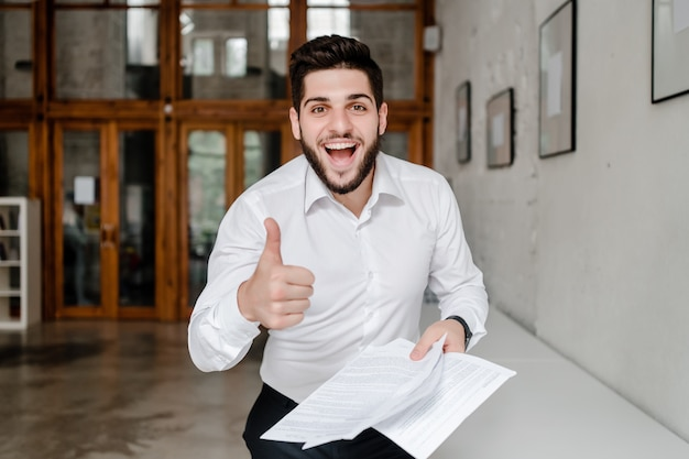 Employé de bureau moyen-oriental heureux souriant et montrant les pouces vers le haut