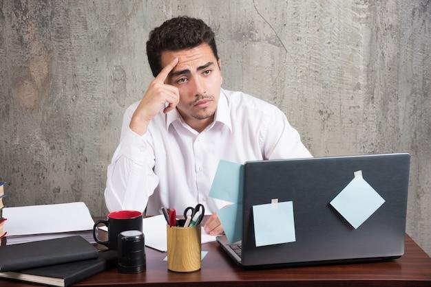 Employé de bureau regardant un ordinateur portable au bureau.