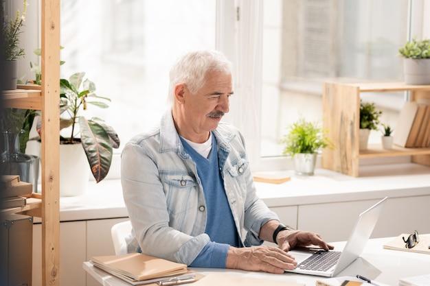Employé de bureau senior occasionnel se concentrant sur l'analyse des données en ligne tout en étant assis par un bureau devant un ordinateur portable