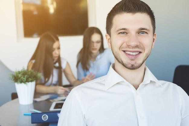 Employé de bureau souriant gros plan portrait avec une équipe de collègues de travail en arrière-plan