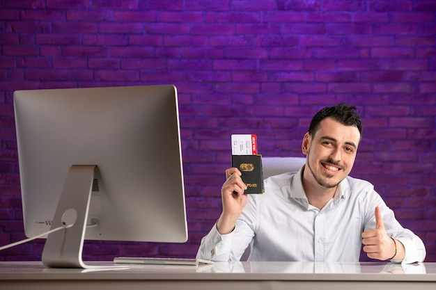 Employé de bureau vue de face assis derrière son lieu de travail tenant des billets et un passeport