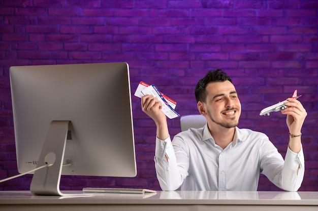 Employé de bureau vue de face assis derrière son lieu de travail et tenant des billets