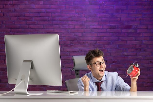 Employé de bureau vue de face derrière un bureau tenant des horloges