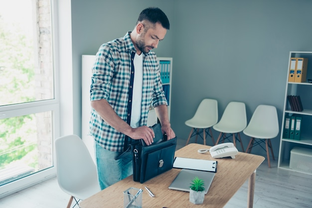 Employé avec une chemise à carreaux bleue travaillant au bureau