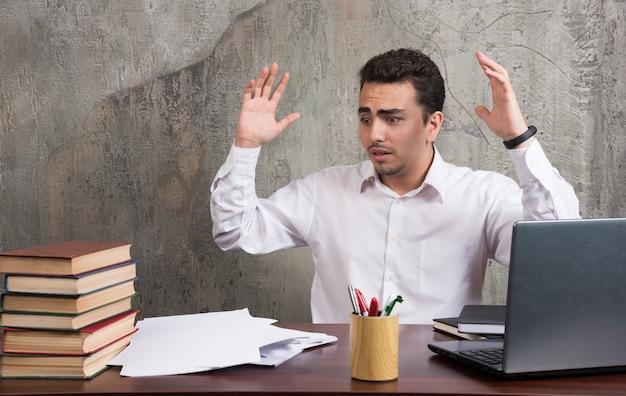 Employé choqué assis au bureau avec des feuilles de papier. photo de haute qualité
