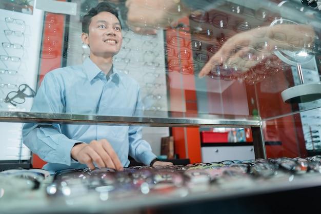 Un employé d'une clinique ophtalmologique sert des consommatrices lors du choix de lunettes à utiliser dans une clinique ophtalmologique