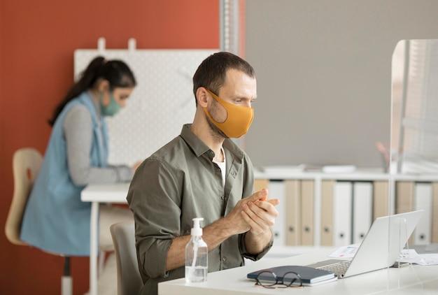 Employé désinfectant les mains au travail