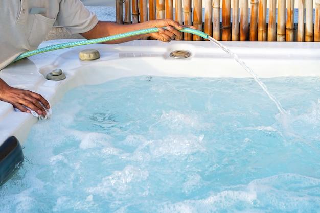 Employé du personnel de l'hôtel africain nettoyant la piscine