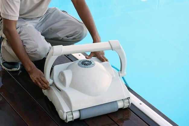 Employé du personnel de l'hôtel nettoyant la piscine