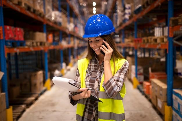 Employé d'entrepôt avec casque ayant une conversation au téléphone et tenant une liste de contrôle dans un entrepôt de distribution