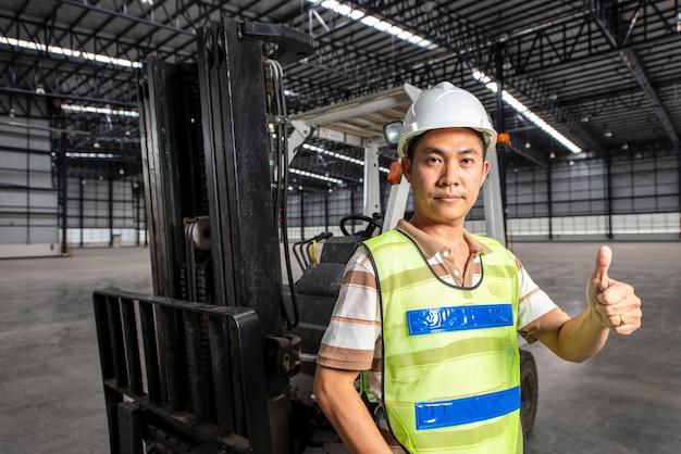 Employé d'entrepôt avec casque de sécurité en face du chariot élévateur dans un nouvel entrepôt moderne