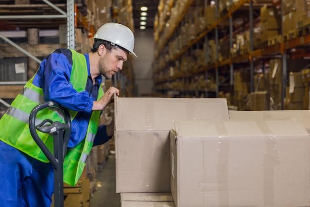 Employé d'entrepôt cochant des cases avec des marchandises en entrepôt