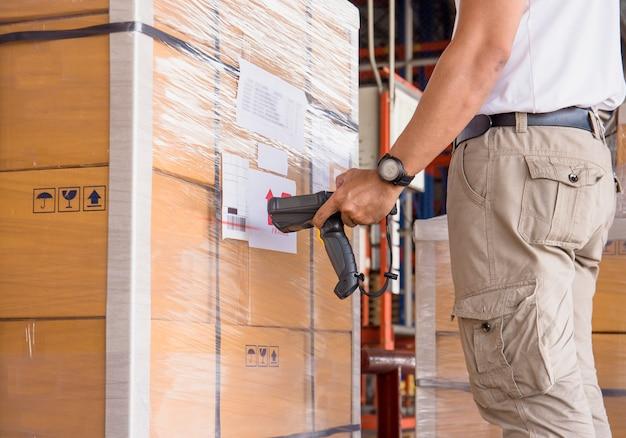 Un employé d'entrepôt tient un lecteur de code à barres avec une numérisation sur la palette d'expédition.