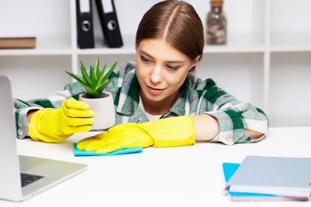 Un employé d'une entreprise de nettoyage essuie la poussière des plantes
