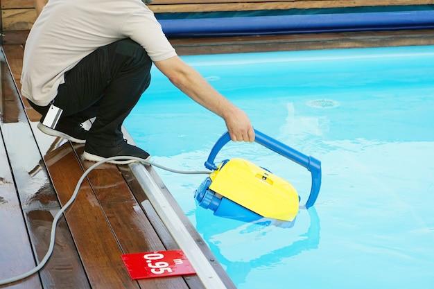 Employé de l'hôtel nettoyant la piscine. nettoyeurs de piscine automatiques.