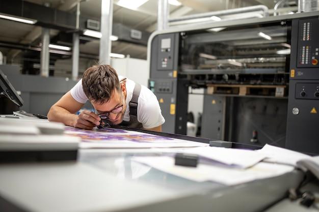 Employé d'impression professionnel vérifiant la qualité de l'impression et la correspondance des couleurs dans l'imprimerie
