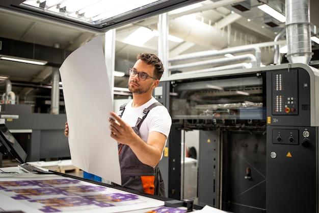 Employé de l'imprimerie vérifiant la qualité de l'impression et contrôlant le processus d'impression.