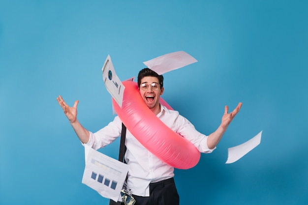 Un employé joyeux disperse des tableaux et des graphiques sur l'espace bleu. homme en chemise blanche posant avec cercle gonflable rose.