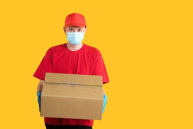 Employé de livraison dans une casquette rouge et un t-shirt, dans un masque et des gants, tient une boîte corona sur jaune