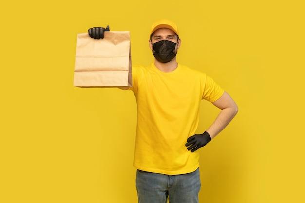 Employé de livreur en chapeau jaune tshirt masque uniforme gant tenir le paquet de papier craft avec de la nourriture isolé