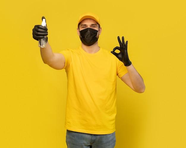 Employé de livreur en uniforme de tshirt jaune, masque stérile, gant tenir bouteille savon désinfectant isolé