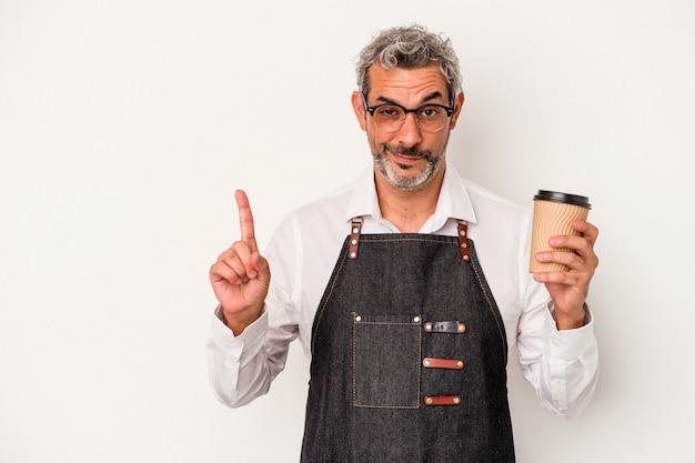 Employé de magasin d'âge moyen tenant un café à emporter isolé sur fond blanc montrant le numéro un avec le doigt.