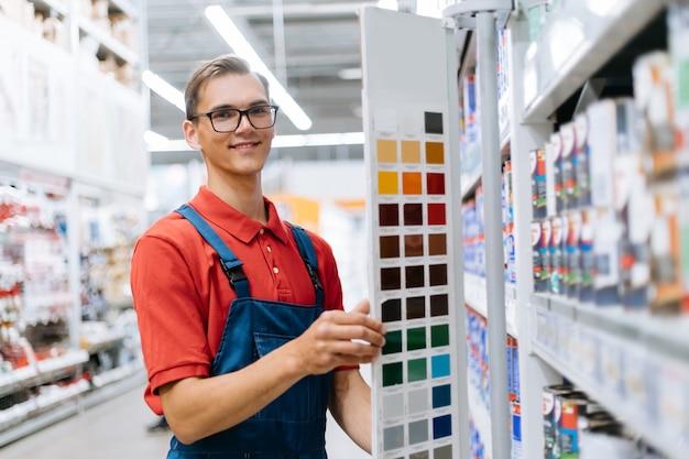 Employé de magasin de construction souriant debout près des échantillons de palette de couleurs