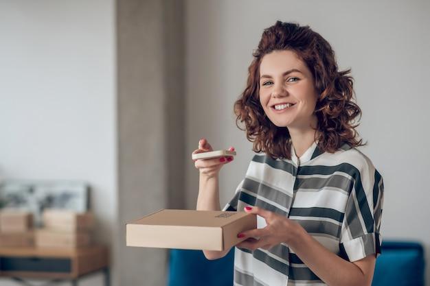 Employé de magasin en ligne joyeux posant pour la caméra sur le lieu de travail