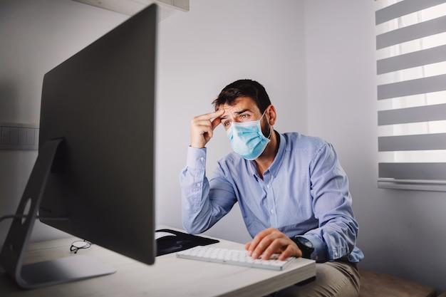 Employé nerveux avec masque assis dans son bureau et lisant un e-mail important pendant l'épidémie de covid