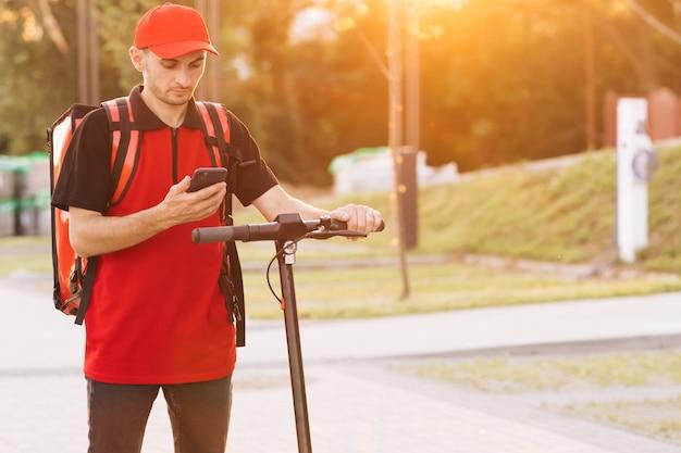 Employé ouvrier livreur livrer commande en ligne client client mâle livraison de nourriture par courrier avec rouge