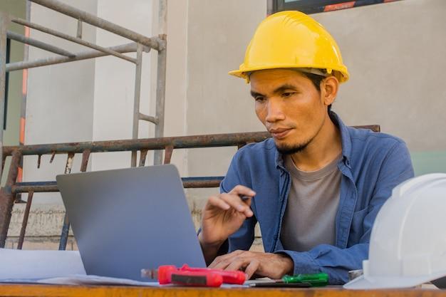 Employé ouvrier travaillant par informatique sur la construction du site