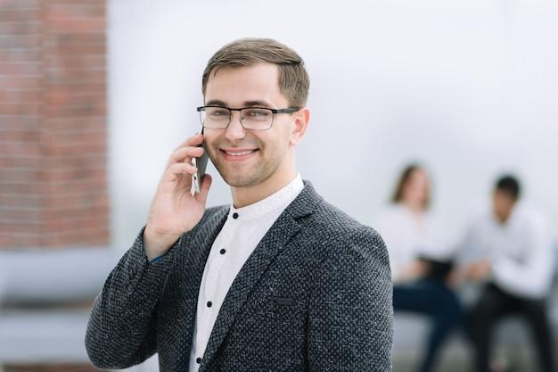 Employé parlant sur un smartphone tout en se tenant dans un bureau moderne. photo avec espace copie