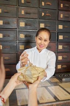 Employé de pharmacie donnant des ingrédients de remède emballés