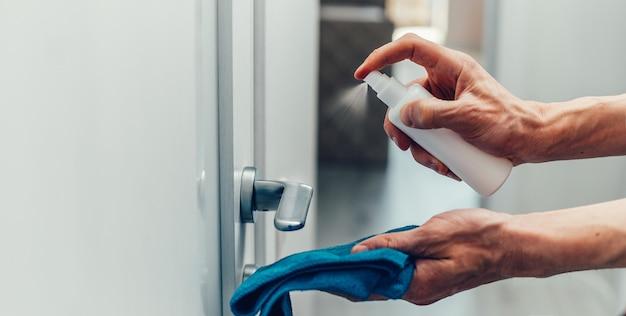 Employé pulvérisant un spray antibactérien sur la poignée de porte